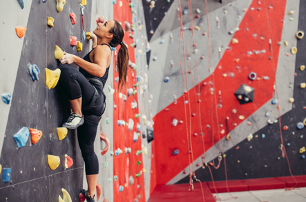 Woman scaling a wall at an indoor rock climbing room.